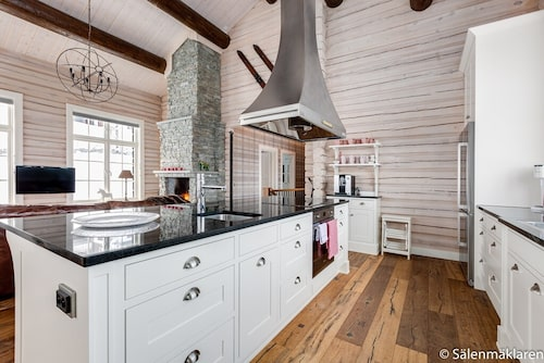Ekgolv i köket och vitlaserade timmerväggar. Takbjälkar och vitlaserad panel i taket. Vitvaror från Smeg.