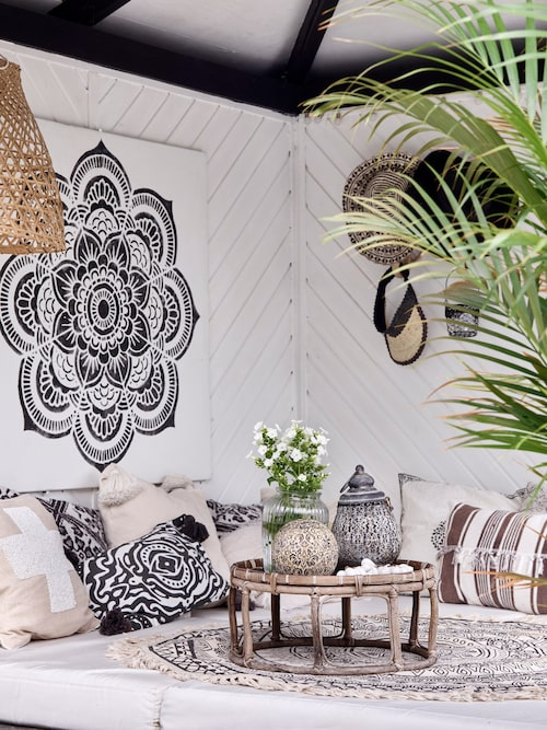 Kirsten har gjort mandalan på väggen med hjälp av en stencil från skovbon.dk. Kuddar från Bungalow Living Bali och H&M Home, resten har Kirsten tillverkat själv. Rund matta, IDE-möbler.