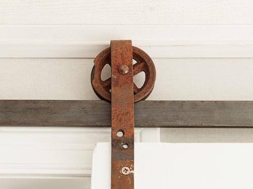 Dörren till sovrummet har hängts upp med hjälp av ett vagnshjul från drängstugan. En av husets många speciallösningar som även berättar om huset historia.