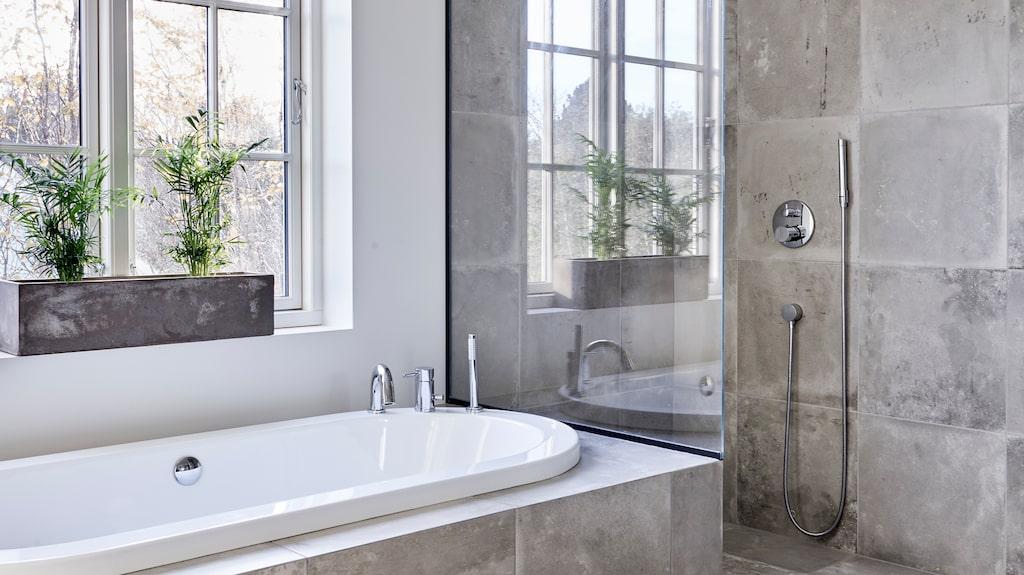 Paret har valt snyggt betongliknande klinker från Höganäskakel som finns både på golvet och vid duschen och badkaret.