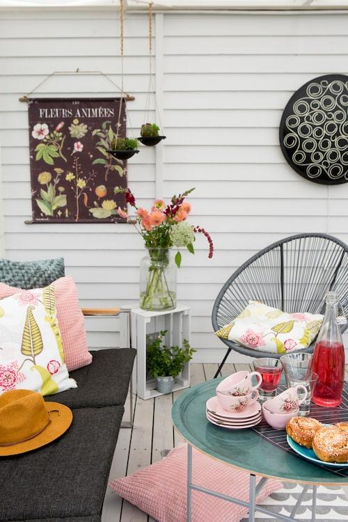 Uterummet är uppdelat i två sektioner. Den ena möblerad med soffa, brickbord från Marimekko samt fåtöljer från Jysk. De rosa kuddarna kommer från Spira.
