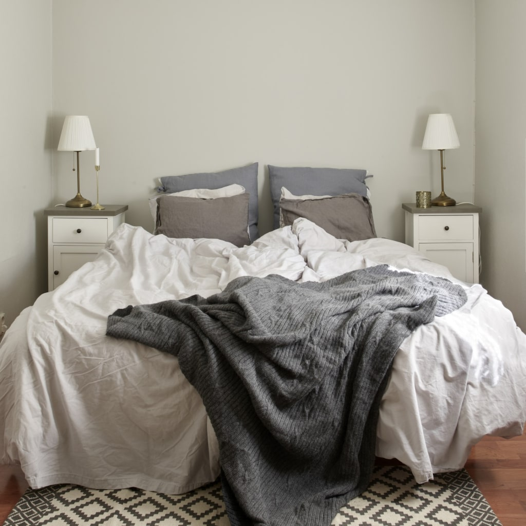 Gråskala. Sovrummet är färgsatt i en ljusgrå nyans. Sängbord från Nilssons i Svedala och sänglampor från Ikea. Sängkläder och matta från H&M home. Grå filt i alpacka från Beach house.