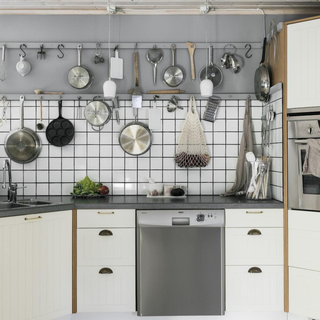 Köket har fått en minimakeover med nya luckor, beslag och nytt kakel i väntan på köksrenoveringen som ska ske under 2018. Kök från Ikea. Knopplisterna har Roger tillverkat, där hänger köksredskap för den dagliga matlagningen.