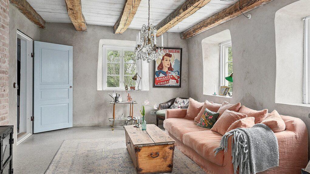 Vardagsrummet på nedre plan. Djupa fönsternischer, betongväggar och takbjälkar av trä.