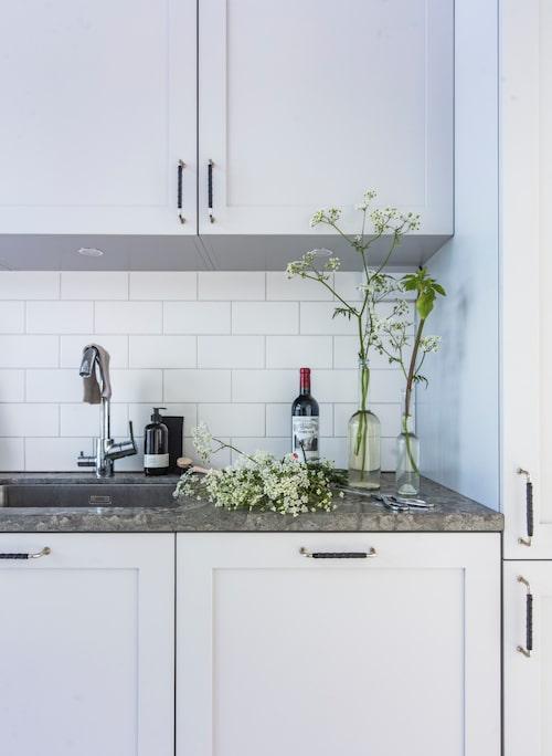 Bänkskivan av kalksten passar fint med de klassiska köksluckorna. Glasflaskor och beige disktrasa, Granit. Diskborste och svart disktrasa, Iris Hantverk.