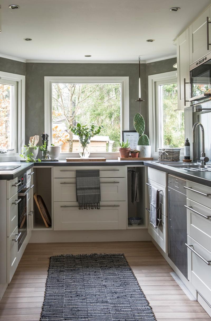 Ljust kök. Köket är byggt i ett burspråk vilket gör att ljuset kommer in från flera olika håll. Handdukar från Lagerhaus.