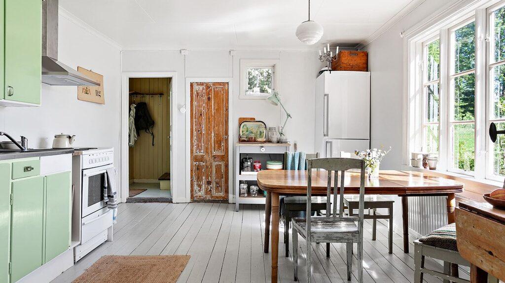 Vackra spröjsade fönster i köket som även har vedspis.