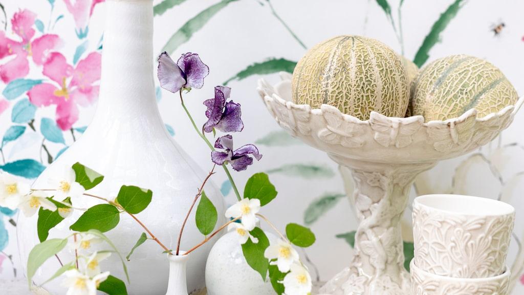 Tapet magnolia och blossom från Sanderson säljs som hel panel eller våd, 137 x 300 centimeter lång, 3 240 kronor, Frank & Cordinata. Hög vas , 310 kronr BP home. Mindre vaser, från höger, 238 kronor, 175 kronor, 188 kronor, alla från Lindform. Fruktskål på fot, 1 725 kronor, muggar Spets, 250 kronor styck, båda från Habitat.