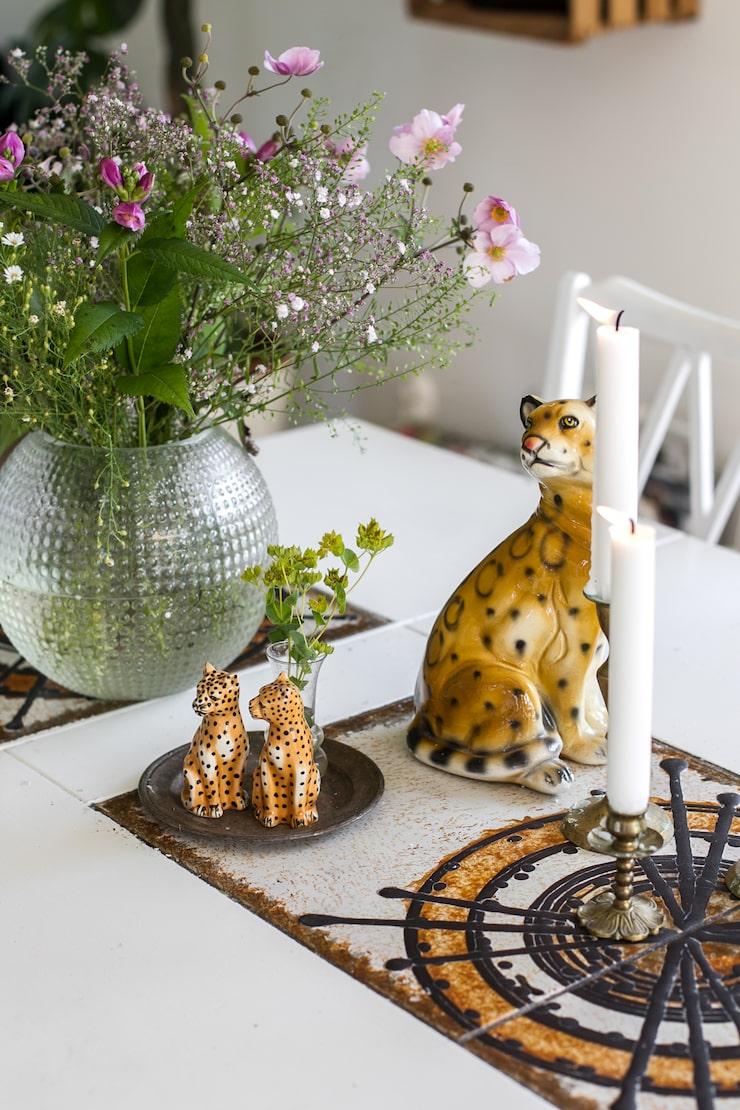 Stora inbyggda kakelplattor ger färg åt den vita matsalen. Här står salt- och pepparkar i leopardform, från HM Home. Den större porslinsfiguren är inhandlad på loppis. Blommor från trädgården och levande ljus är återkommande inslag i Cornelias stilleben.