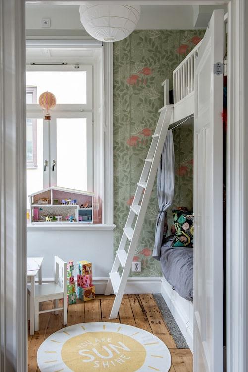 Dottern Selmas rum har en platsbyggd våningssäng. Tapet Nautilus No 3, Cole & Son. Mönstrad kudde, Littlephant. Matta, H&M Home. Luftballong i fönstret, Royal Aero. Byggklossar, Djeco.