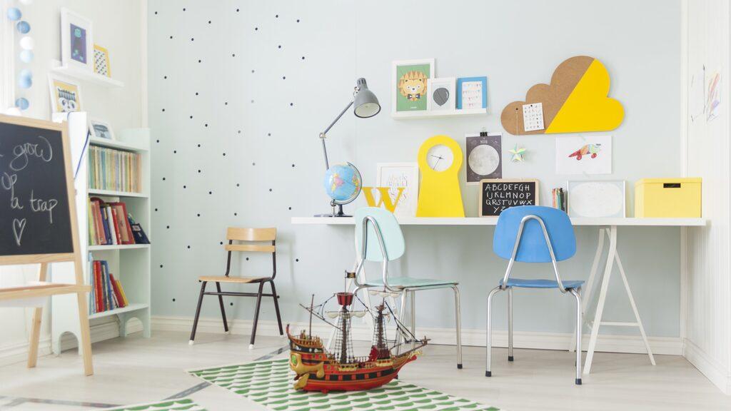 Skrivbord, klocka och lampa från Ikea. Stolarna är ett loppisfynd. Två av stolarna har paret sprejmålat. Bokhyllan är ett arvegods som målats om. Mattorna är från Amazon.