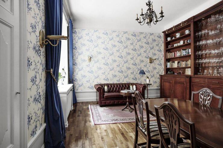 Vardagsrummet har vita tapeter med blå blomstergirlander.