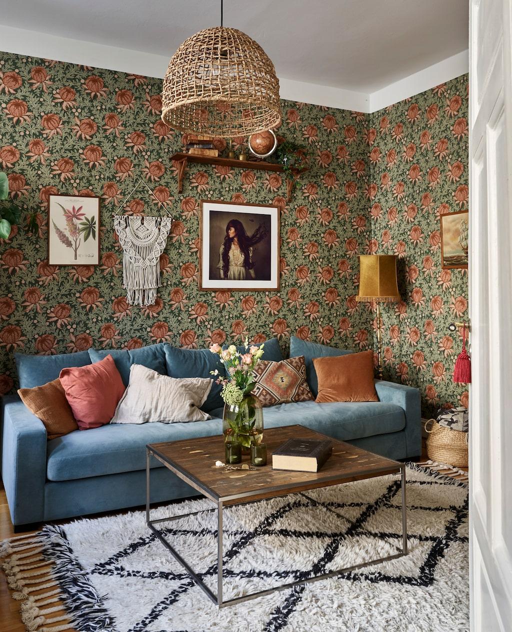 Vardagsrummets förr vita väggar har klätts med en storblommig tapet, som i ett bohemiskt bibliotek.