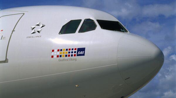 Flygplanets namn står under flaggorna framme vid cockpit.