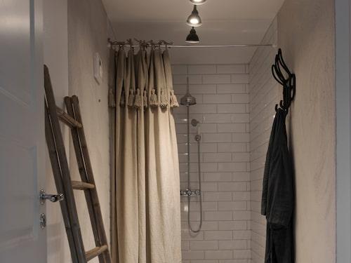 I badrummet har delar av väggen kaklats och vissa delar blivit putsade. Duschdraperi från Fira habitat, bambustege från Granit och pall från Tine K home.