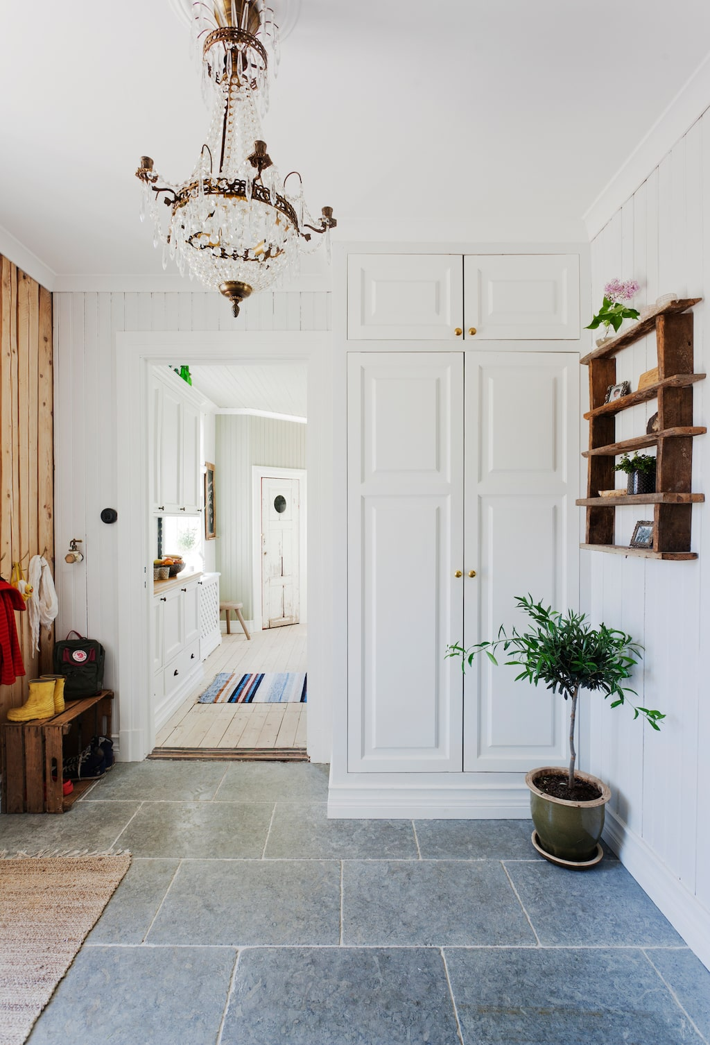 Förvaringen för ytterkläder och skor är byggd av Johan. Stengolvet kommer från Stiltje, takkronan från Auktion 3 och hyllan från auktion. En gammal trälåda har blivit skohylla till barnen.