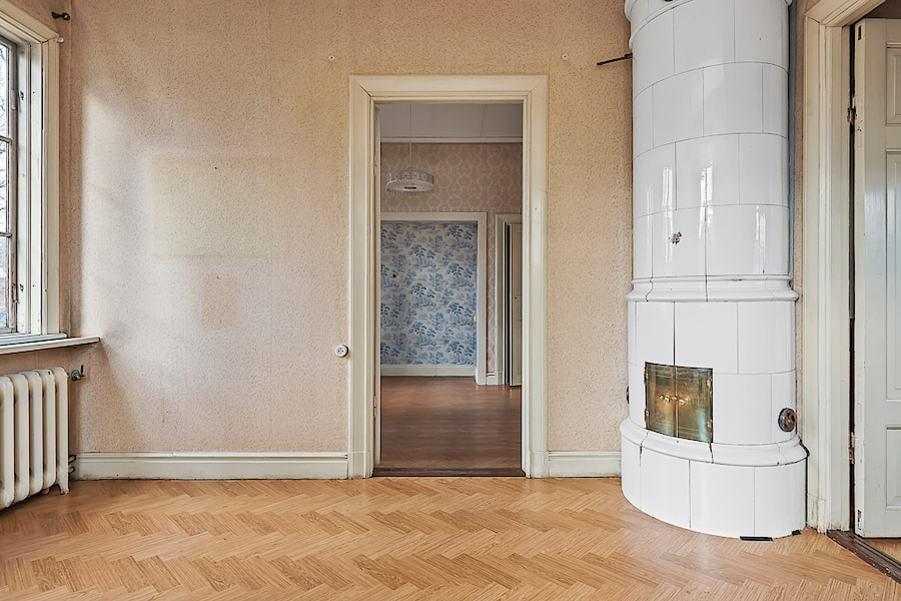 Ett av tre sovrum. Ljusinsläpp från två väderstreck, tapetserade väggar, laminatgolv och vacker kakelugn.
