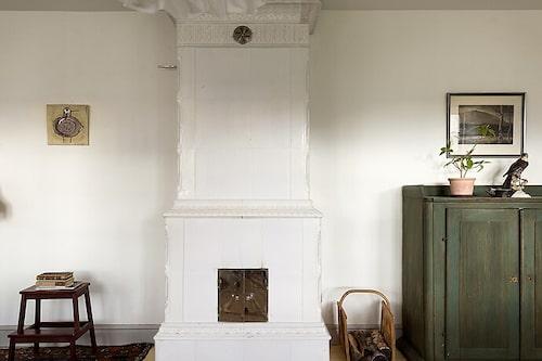 I vardagsrummet står en tidsenlig kakelugn från Rörstrand.