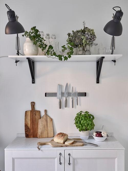 Praktisk hörna vid fönstret i köket. Hylla, skåp och lampor, Ikea. Kruka, från Kähler. Knivar, Global. Kruka för färska kryddor, från Lagerhaus.
