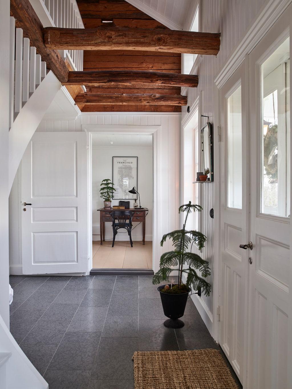 I hallen är de gamla gedigna takbjälkarna synliga, en fin kontrast till de vita väggarna. Innanför hallen ligger hemmakontoret.
