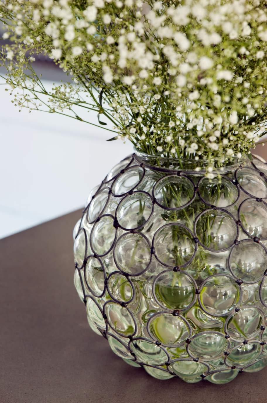 Glasvasen med metallhölje kommer från Manzana och matchar kökets kakel med sina runda former.