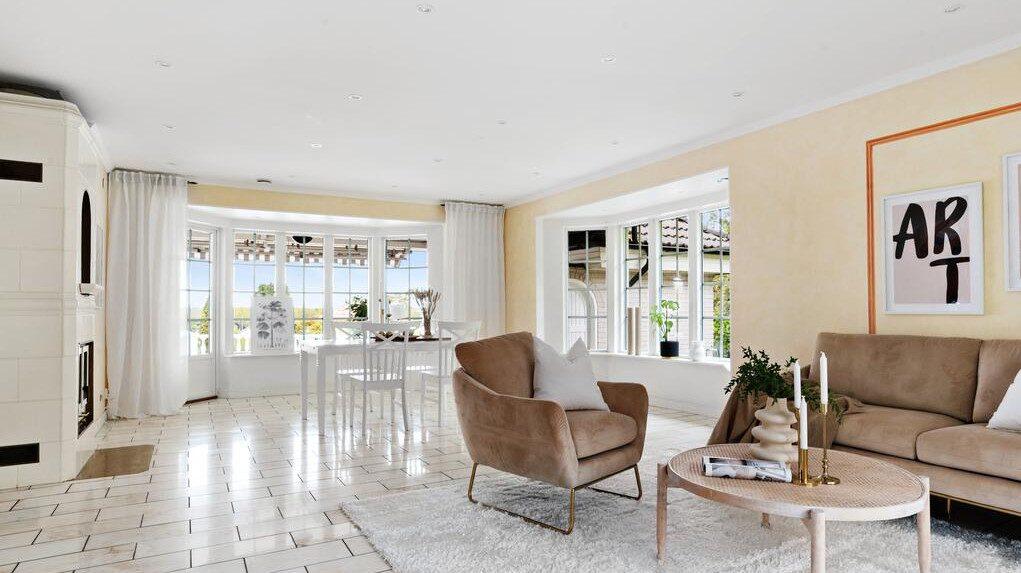 Vardagsrum med marmorgolv, fönster åt tre håll, spotlights i taket, eldningsbar eldstad samt utgång till pooldäcket.
