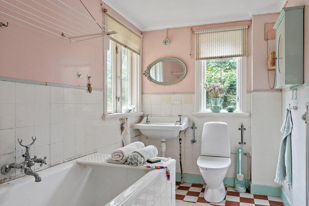 Här finns ett charmigt äldre badrum i pastellfärger.