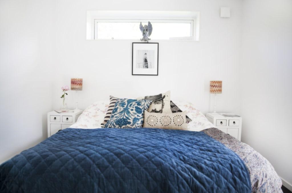 Rogivande. Sovrummet har en neutral bas och dealjer i turkos och blått. Lampor från Missoni.