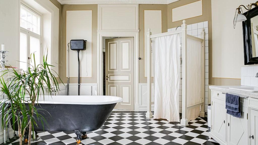 Badrummet har gjorts tidsenligt med egensnickrad duschhörna med skynken, kommod med marmorskiva och badkar på fötter samt schackrutigt golv.