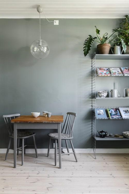 I köket finns en liten frukostplats, övriga måltider intas vid matsalsbordet. En Stringhylla balanserar sekelskifteskänslan i rummet. Köksmöblemanget är loppisfyndat.