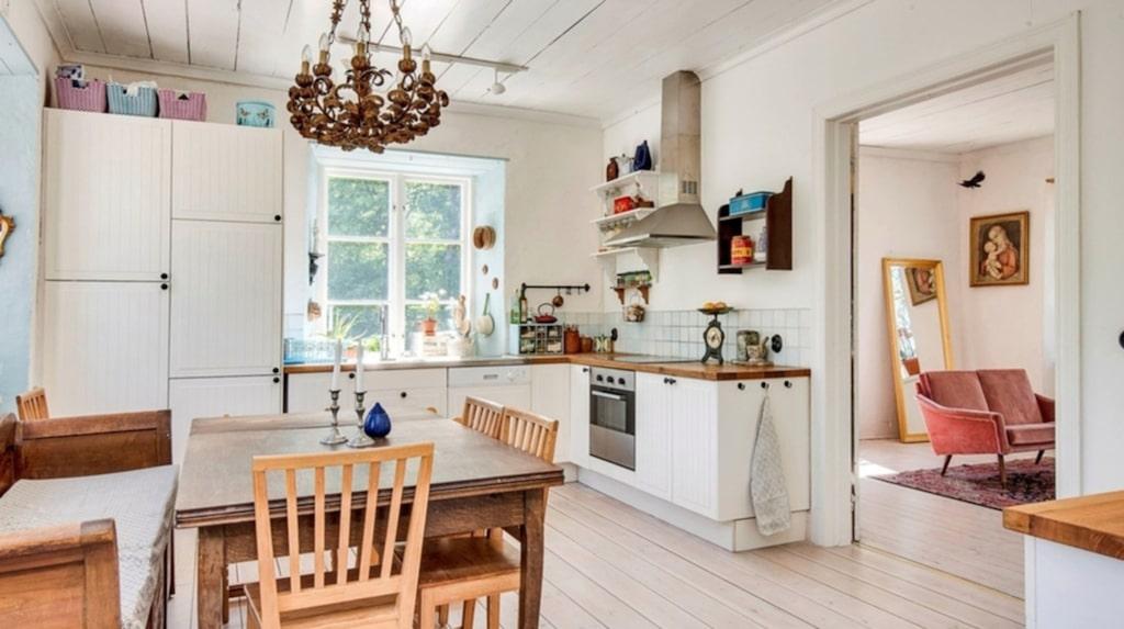 Köket har grålutat furugolv och vitkalkade väggar.