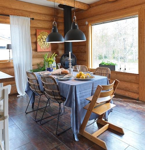 """Köksbord och stolar är från Jysk, taklampa från By Rydén. Duken är från Himla/Vågskvalp Inredning. Frida och Emil fick en hel del möbler av tv-programmet """"Sofias änglar"""" när de medverkade där hösten 2019. Däribland den takhängda braskaminen från Nordpeis. Tavlan med lejonet är målad av Minnas Art & Vintage."""