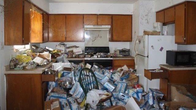Köket går inte ens att gå in i på grund av alla tomma ölburkar och kartonger. Kolla även in de stora spindelnäten som hänger från taket!