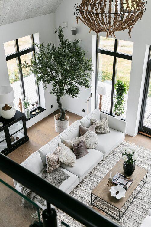 Ett rum med högt i tak kräver stora växter. Det konstgjorda olivträdet hjälper till att sudda ut gränsen mellan ute och inne.