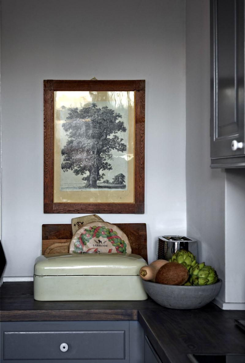 Tavlan är arvegods från Frederiks mormor och ett precis likadant träd finns numera i trädgården. Brödlådan är ett loppisfynd.