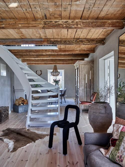 När Anna och hennes pappa renoverade huset tog de bort innerväggarna till de små rummen. I stället finns här nu ett enda stort rum som löper längs hela husets långsida. Trappan som står i mitten leder upp till övervåningen.