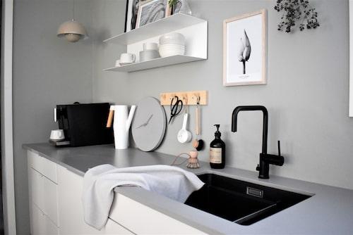 Mattsvart blandare, Nivito. Vägghylla, Ikea. Klocka, Bruka design.
