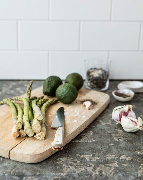 Köksväggen är klädd med vitt kakel. Kniven och skärbrädan har funnits på ön länge. Småskålar för flingsalt och peppar, Indiska. Glas, Ikea.